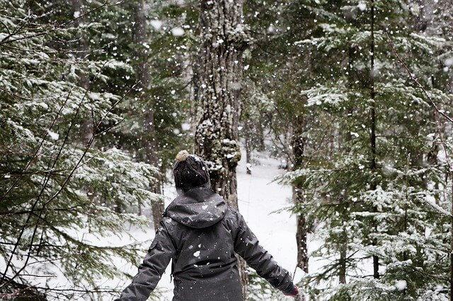 """alt=""""ダウンコートを着た女性が自然の中にいる"""