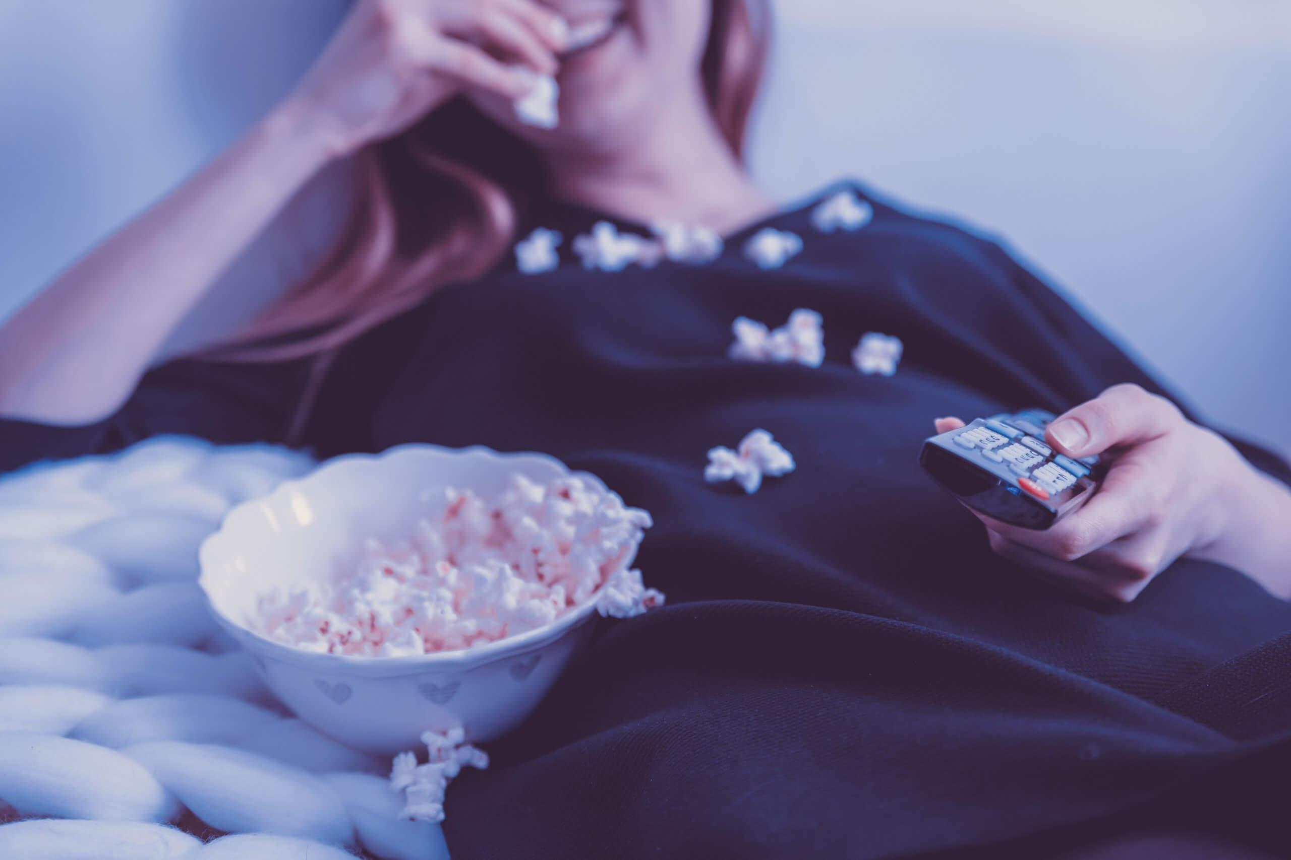 ベッドでポップコーンを食べてる女性